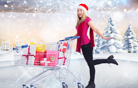 Festive blonde pushing trolley full of gifts against snowy landscape with fir trees
