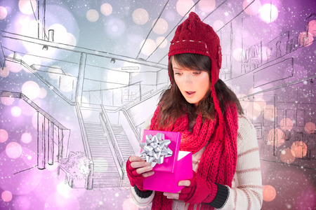 Festive brunette opening a gift against light glowing dots on purple