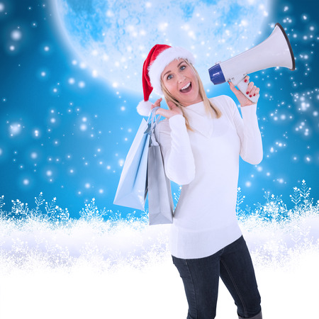 Festive blonde holding gift bags and megaphone against blue background with vignette