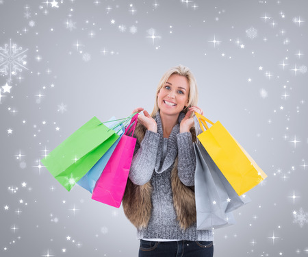 Blonde in winter clothes holding shopping bags against grey vignette