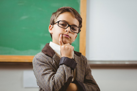 Portrait of pupil dressed up as teacher thinking in a classroom