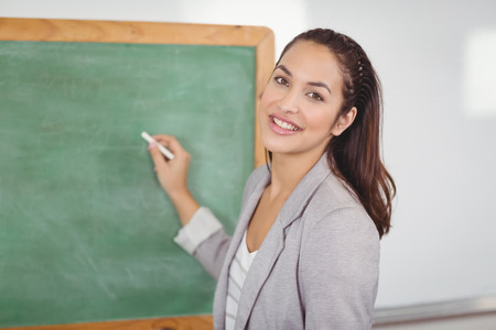 Portrait of pretty teacher writing on chalkboard in a classroom in school