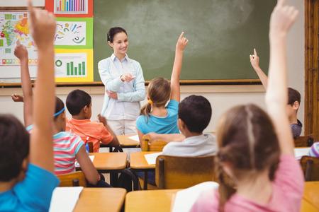 Photo pour Teacher asking a question to her class at the elementary school - image libre de droit