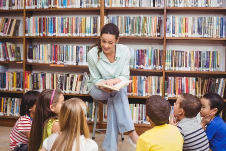 Photo pour Teacher reading her pupils a story at the elementary school - image libre de droit