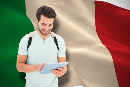 Student using tablet pc against digitally generated italian national flag