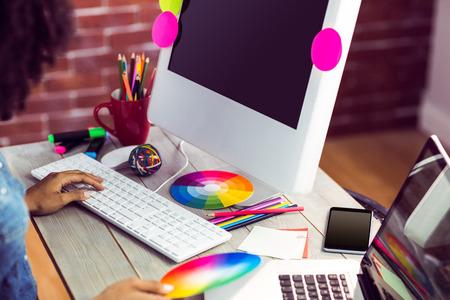 Female graphic designer working at desk against red brick background
