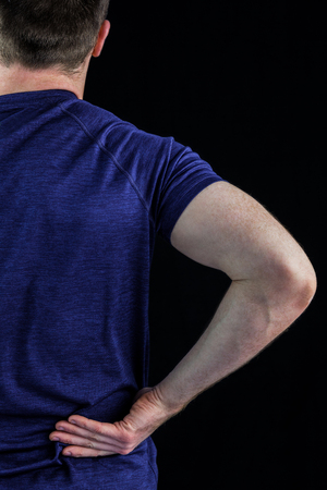 Rear view of a man with back pain over over black background