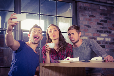 Grimacing friends taking selfies at coffee shop