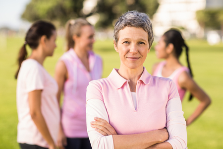 Portrait of woman wearing pink for breast cancer in front of friends in parkland