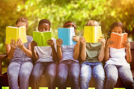 Photo pour Children reading books at park against trees and meadow in the park - image libre de droit