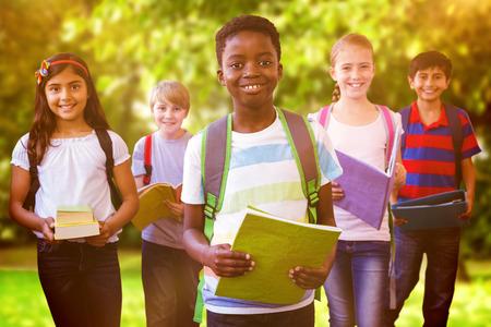 Foto de Smiling little school kids in school corridor against trees and meadow in the park - Imagen libre de derechos