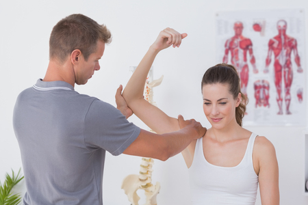 Doctor stretching a young woman arm in medical office