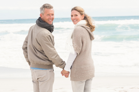 Happy couple holding hands while walking at the beach