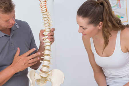 Doctor showing anatomical spine to his patient in medical office