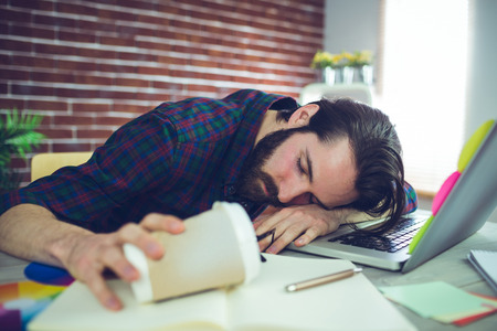 Tired editor holding disposable cup while sleeping on office desk