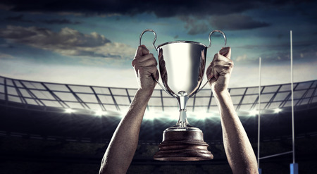Successful rugby player holding trophy against rugby stadium