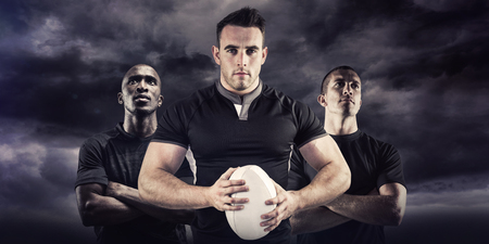 Tough rugby player looking at camera against blue sky