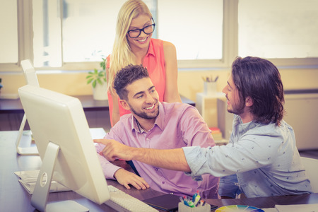 Businessman pointing on computer as smiling colleagues looking at it in office