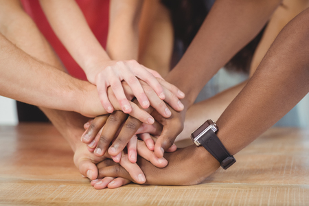 Photo pour People putting their hands together at desk - image libre de droit