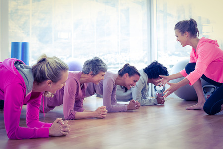 Foto de Smiling group of women exercising on floor in fitness studio - Imagen libre de derechos