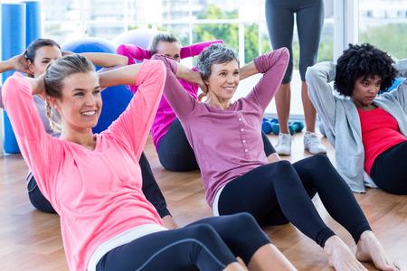 Attractive women doing sit ups on hardwood floor in fitness studio