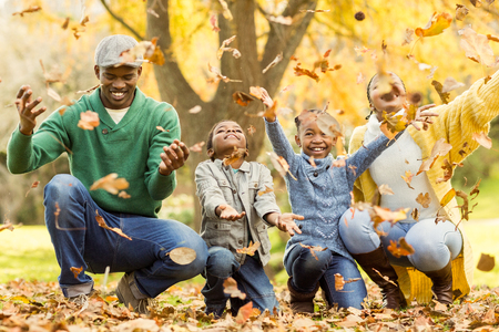 Young smiling family throwing leaves around on an autumns day