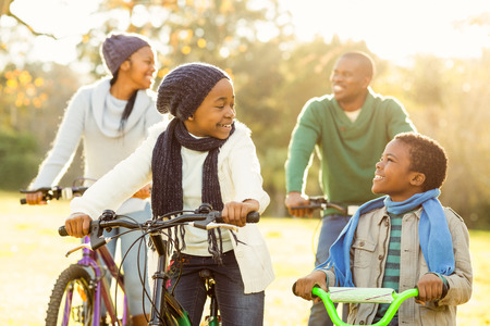 Young smiling family doing a bike ride on an autumns day