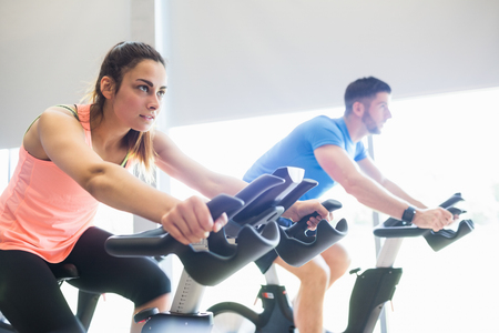 Photo pour Man and woman using cycling exercise bikes at the gym - image libre de droit