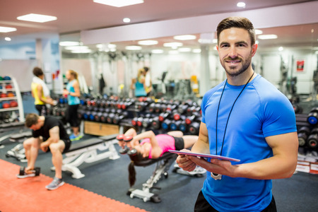 Photo for Handsome trainer using tablet in weights room at the gym - Royalty Free Image