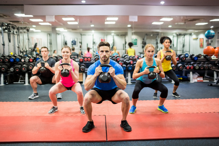 Foto de Fit people working out in fitness class at the gym - Imagen libre de derechos