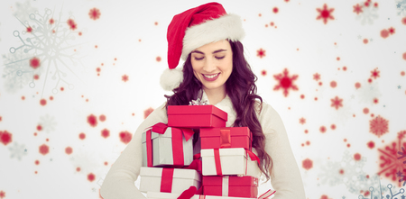 Festive brunette holding pile of gifts against snowflake patternの写真素材