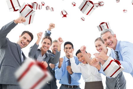 Business people cheering in office against white and red gift boxの写真素材