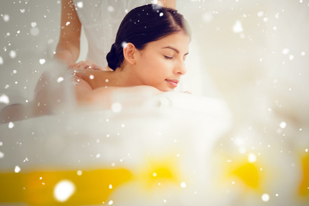 Snow against woman enjoying a salt scrub massage