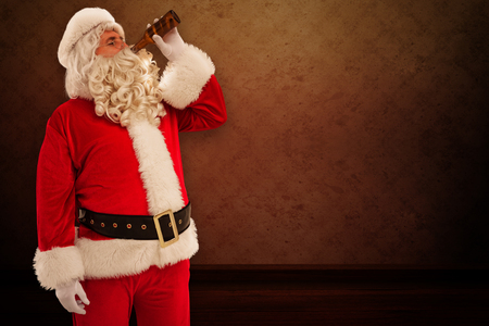 Father christmas drinking a beer against room with wallpaper