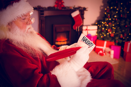 naughty or nice against santa claus writing list on scroll