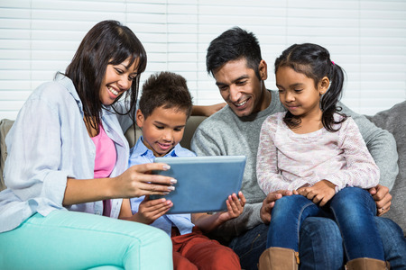Smiling family on the sofa using tablet in living room
