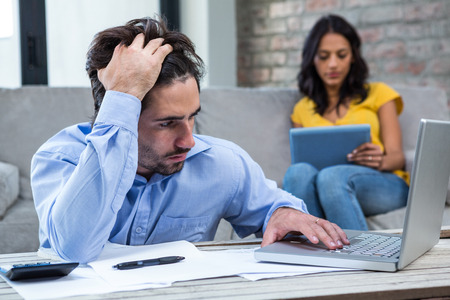 Worried man paying bills in living room while wife is on the sofa
