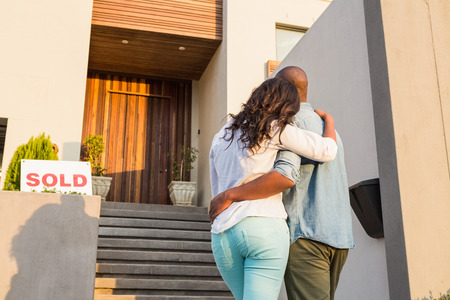 Back view of couple with arms above after buying house
