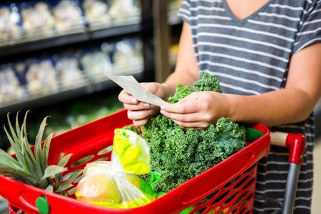 Foto für Woman with red basket holding list in supermarket - Lizenzfreies Bild