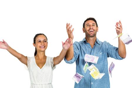 Happy couple throwing money on white screen