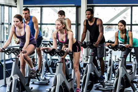 Photo pour Fit people working out at spinning class in the gym - image libre de droit