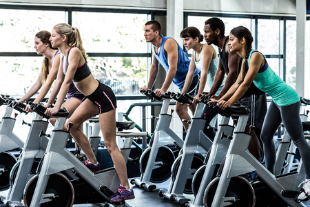 Foto de Fit people working out at spinning class in the gym - Imagen libre de derechos