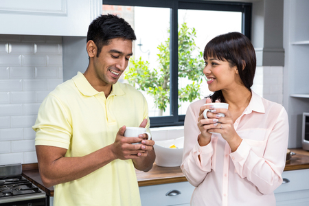 Photo for Happy couple talking and holding cups in the kitchen - Royalty Free Image