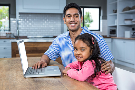 Smiling father using laptop with his daughter in the kitchen