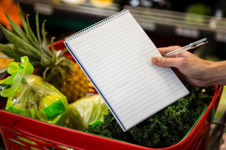 Foto für Close up view of a shopping list against a full basket - Lizenzfreies Bild