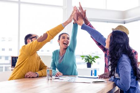 Foto de Cheerful business team doing high five while sitting in creative office - Imagen libre de derechos