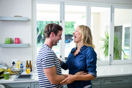 Cute couple dancing and laughing in the kitchen