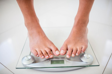 Photo pour Feet of woman on weighting scale at home - image libre de droit