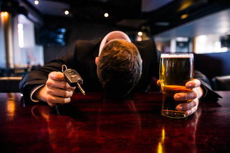 Drunk man holding a beer and car keys in a bar