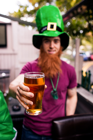 Disguised man holding a pint for St Patricks day